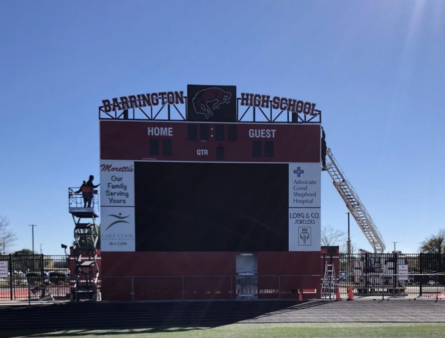 """Workers make adjustments to the new scoreboard. Some student athletes were very happy about the upgrade because the old scoreboard had some technical issues. """"I think that the changes to the stadium are really cool,"""" said junior AJ Salam. """"Every year I've been playing football the scoreboard has worked half of the time, so it was a good idea building a new one."""" Photo by Camille Wodarz."""