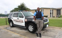 New school cop, Hakeem Smith, poses in front of his patrol car. Smith's goal is to form a positive relationship with all students. Photo by Camille Wodarz.