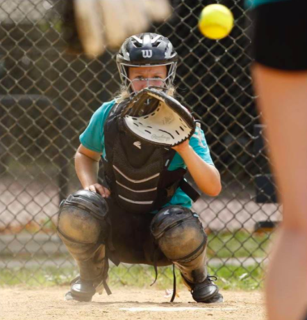 "Waiting for the ball, Sophomore Tessa Peterson stands ready and in position to receive it. Since being assigned as a catcher in eighth grade, Tessa worked hard and maintained her title as catcher despite the inconveniences thrown her way. ""I play on a travel team and so we were able to play all summer with some restrictions,"" Peterson said, explaining how she still played in her position today. Photo by Stacey Wescott"